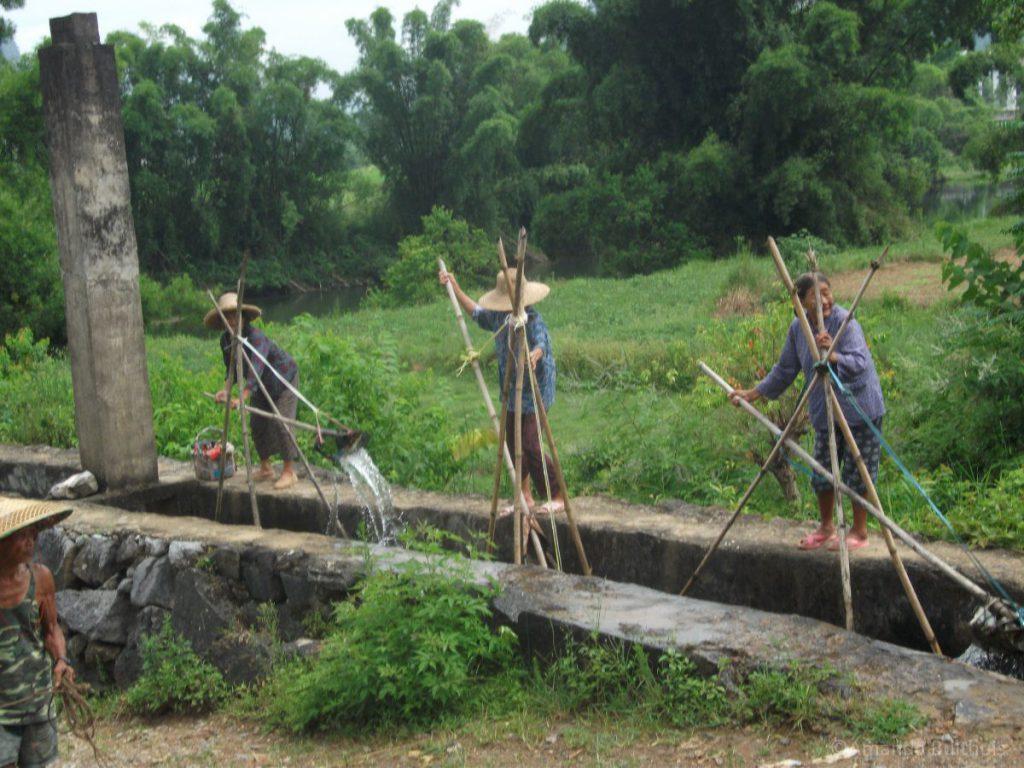 Vrouwen die water pompen uit een rivier